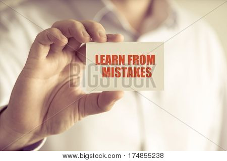 Businessman Holding Learn From Mistakes Message Card