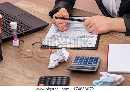 Woman Use Calculator With Laptop For Filling 1040 Tax Form.