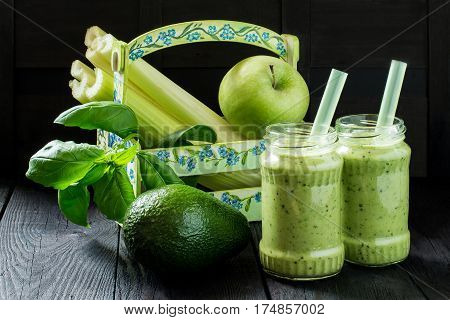 Jars of vitamin green smoothie in the box and ingredients for cooking on a wooden table. Concept of healthy or vegetarian food