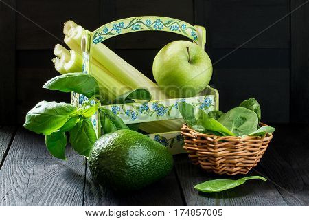 Ingredients for making green smoothies vitamin (apple celery avocado spinach basil) in a box on a dark wooden table. Concept of healthy or vegetarian food