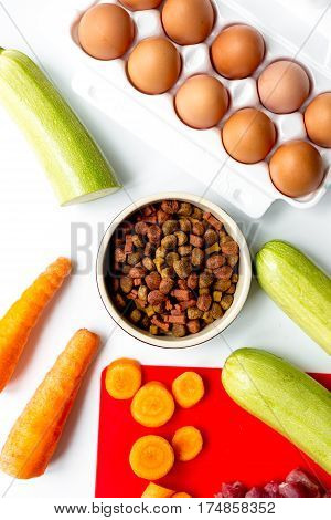 Bowl of dry dogfood with fresh carrot, courgette and cut meat on white table background top view