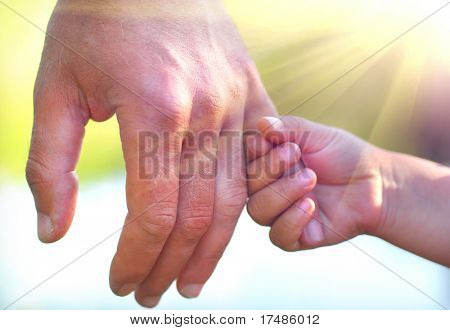 a little girl holding her father´s finger