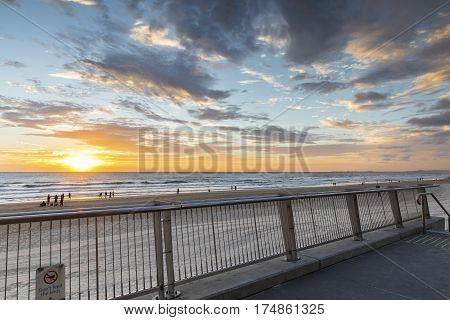 People walking on the beach at Surfers Paradise Gold Coast, with colourful sunrise in horizon