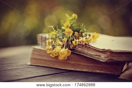 Bouquet of yellow buttercups on old books on a wooden table.