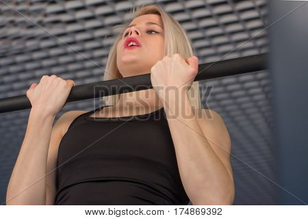 Sexy fit woman performing pull ups in a bar.
