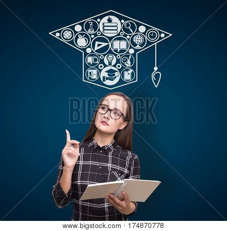 Portrait of a geek girl holding a book and wearing glasses while standing near a dark blue wall with an education sketch on it.