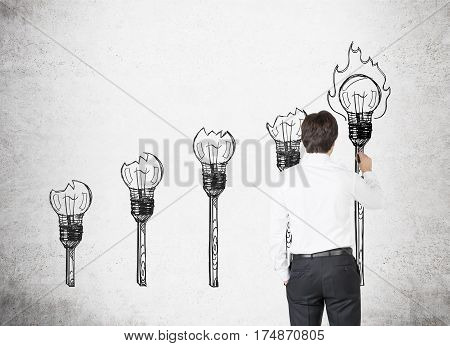 Rear view of a businessman drawing light bulb torches on a concrete wall. Concept of inspiration in business.