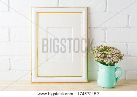 Gold decorated frame mockup with wild very soft pink flowers in mint pitcher near painted brick wall. Empty frame mock up for presentation design. Template framing for modern art.