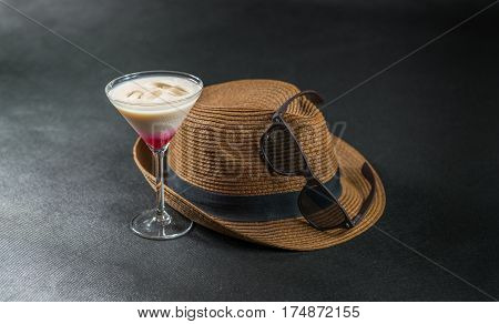 colored drink a combination of red beige and violet martini glass brown sunglasses brown stylish hat party set