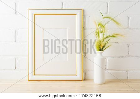 Gold decorated frame mockup with yellow and green wild grass ears in styled vase near painted brick wall. Empty frame mock up for presentation design. Template framing for modern art.