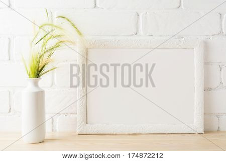White landscape frame mockup with yellow and green wild grass ears in styled vase near painted brick wall. Empty frame mock up for presentation design. Template framing for modern art.