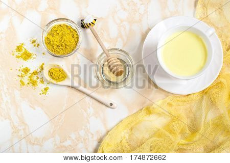 Healthy drink: milk with turmeric and honey known as the golden milk. Detox burns fat boosts immunity disease prevention. Flat lay top view