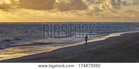 Unidentified ocean shorline runner on beach at sunrise