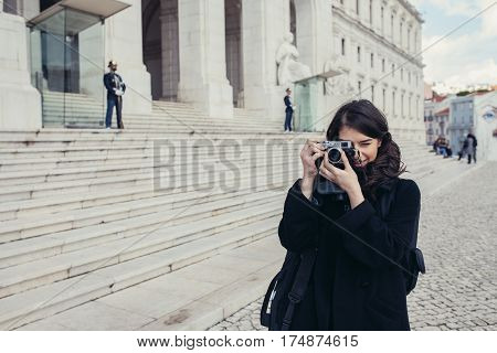 Female tourist photographer making some travel photos of Assembleia da Republica in Lisbon.Smiling is woman admiring watching monumental building of Parliament in Portugal