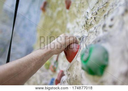 The Man's Hand Climbing On An Artificial Wall