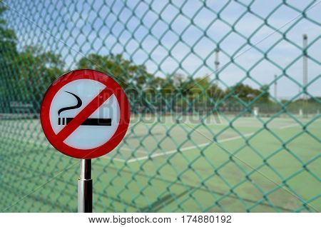 No smoking sign in front of blurred tennis court background healthy concept