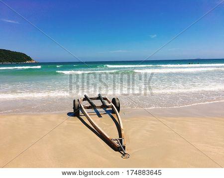 The Wheelbarrow On The Beach With Sea Wave Foam