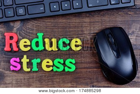 Reduce stress words on wooden table closeup