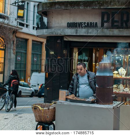 PORTO, PORTUGAL - MAR 2, 2017: Unknown street vendor on one of the streets in the old downtown. City of Porto was elected from 20 selected Best European Destination 2017 and won this prestigious title