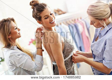 Happy woman trying on a dress in shop