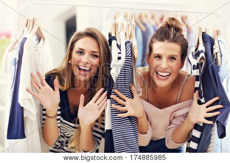 Happy friends shopping for clothes