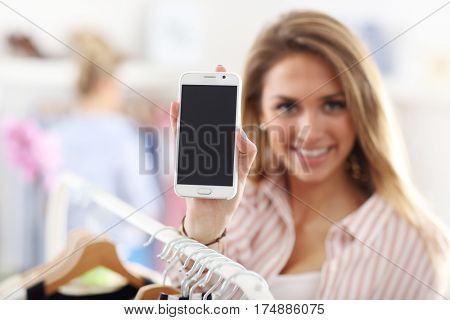 Happy woman in clothes shop holding smartphone