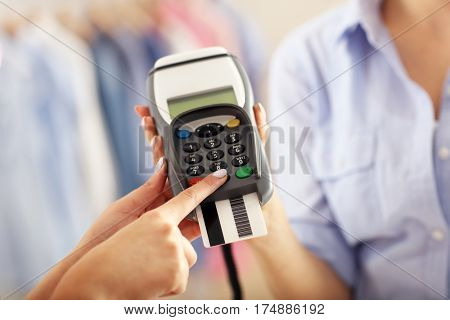 Closeup mid section of female customer paying in shop with credit card