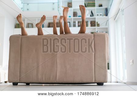 Feet of happy children at home on sofa playing