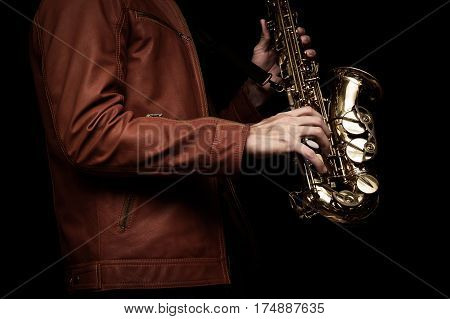 male jazz saxophone player on the stage with brown leather jacket