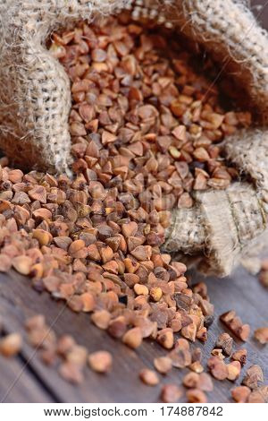 Brown buckwheat in a bag spilling on wooden table