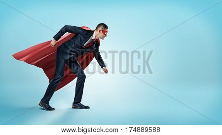 A businessman in a superhero red cape and a mask standing in starting line position on blue background. Business and competition. Ready to work. Winners and losers.