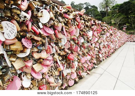 Lovers Person Showing Love By Use Master Key Lock On Steel Net At Love Lock Penang Hill