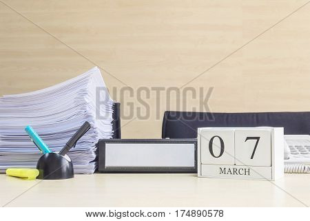 Closeup white wooden calendar with black 7 march word on blurred brown wood desk and wood wall textured background in office room view with copy space selective focus at the calendar