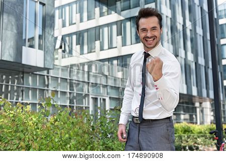Portrait of happy businessman with clenched fist standing outside office building