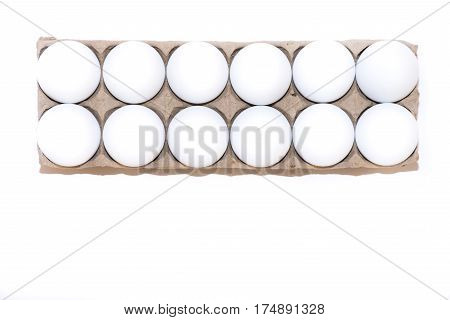 A dozen white hen's eggs in a tan cardboard carton against a white background from above with copy space.