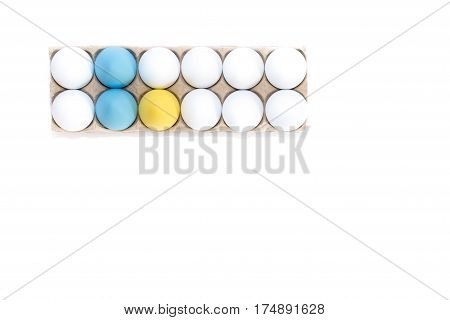 Two Easter eggs dyed blue, one dyed yellow and nine white hard boiled hen's eggs in a cardboard carton photographed from above against a white background with copy space.