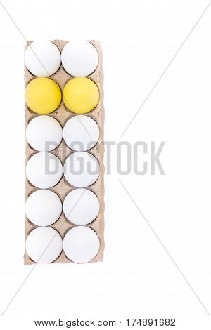 Two Easter eggs dyed yellow and ten white hard boiled hen's eggs in a cardboard carton photographed from above against a white background with copy space.