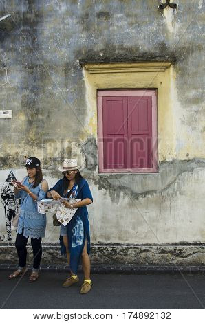 Two traveller thai women reading guide book for tour Georgetown city and find street art picture on wall in Penang Malaysia.