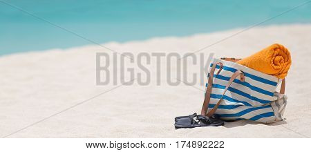 panorama of beach bag towel and flip-flops at white sand perfect caribbean beach with turquoise water in the background at anguilla island vacation concept copyspace on the left