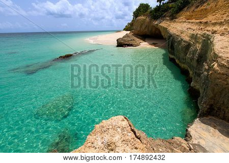 view of rocky rugged shore with white sand beach and turquoise lagoon at anguilla island