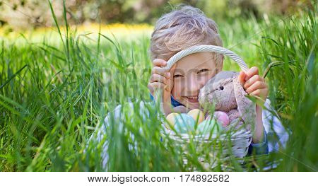 smiling happy boy holding basket with easter eggs and bunny toy after easter egg hunt lying in green grass in the park copyspace on the left