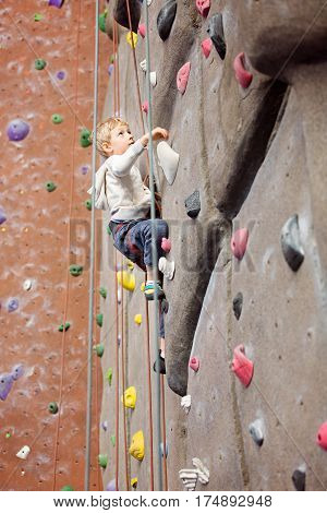 brave little boy rock climbing at indoor climbing gym healthy and active lifestyle