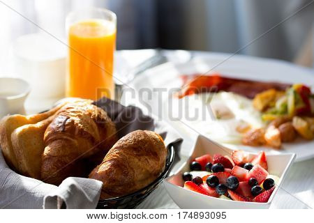 delicious healthy fruit bowl for breakfast with orange juice and pastries in the background in-room dining at the hotel