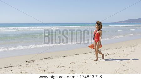 Lifeguard with rescue float walking along beach