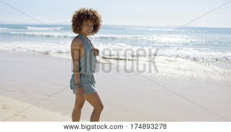 Female wearing jumpsuit walking along beach