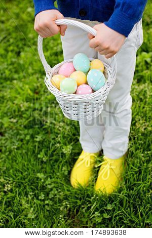 little boy holding white basket with easter eggs after egg hunt standing at grass in the park