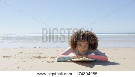 Woman lying on a surfboard