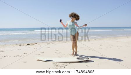 Female listening music and dancing on beach