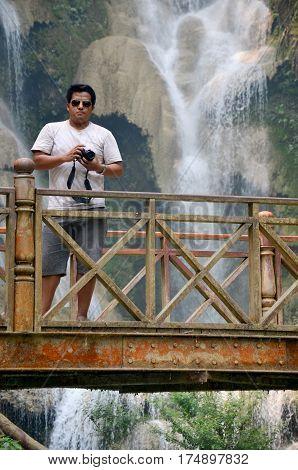 People travel and stand on the bridge looking and take photo viewpoint of Kuang Si Falls or Tat Kuang Si Waterfalls in Luang Prabang Laos