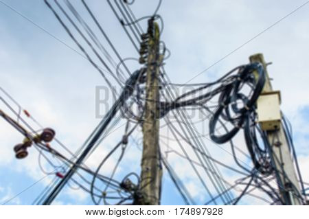 blurred High voltage power pole with wires tangled,Wire and cable clutter. Potential danger from a mess of wires , Electric pole with electric wire tangled,very messy electricity or telephone pole.